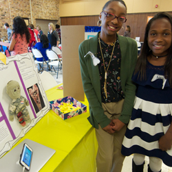 Students discuss their research during community event.